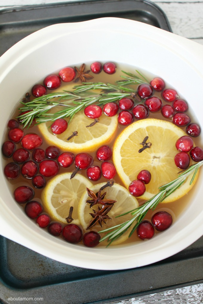 crock pot of water filled with orange slices, cranberries, cloves, and rosemary.