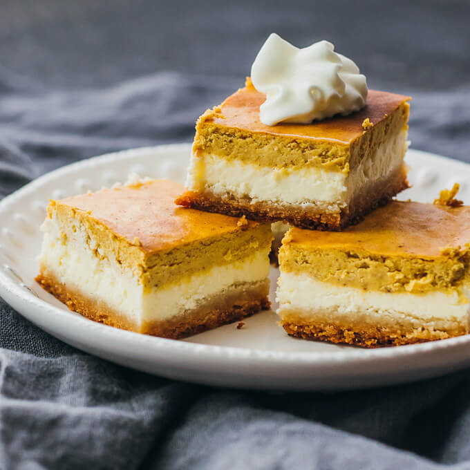 pumpkin cheesecake bars cut in squares and stacked on a plate