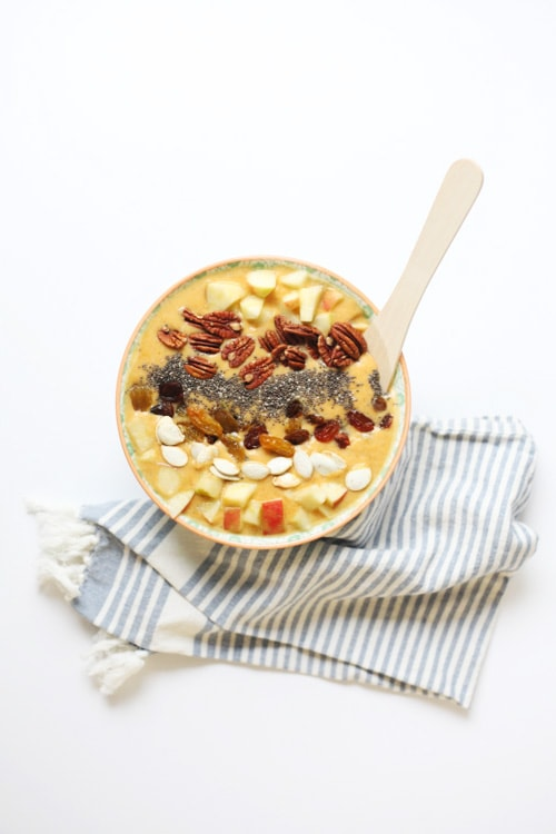 pumpkin smoothie bowl topped with nuts and diced apples