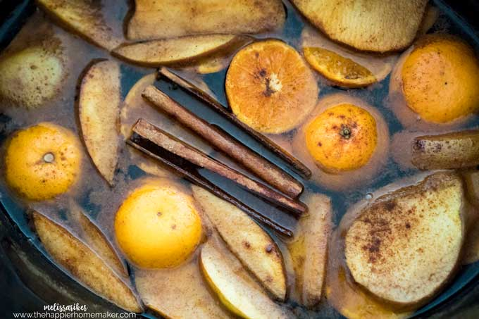 sliced oranges, pears, lemons and cinnamon sticks in a pot full of water